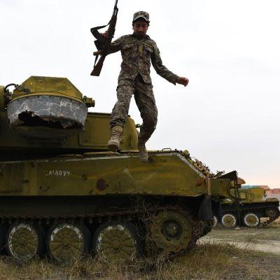 Afganistanin sotilas siesoo panssarivaunun katolla.
