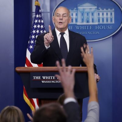 Kuvassa Valkoisen talon kansliapäällikkö John Kelly on puhumassa toimittajille. Etualalla viittaavia käsiä.