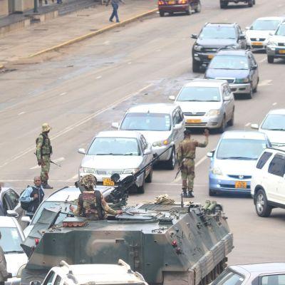 Panssarivaunu kadulla, sen takana kaksi letkaa autoja.