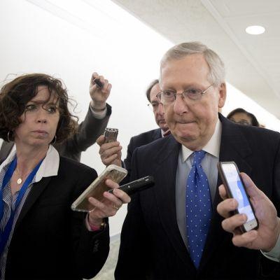 Mitch McConnell kulkee valkoisessa käytävässä nauhureita pitelevien toimittajien ympäröimänä. McConnellilla on tumma puku ja sininen valkopilkkuinen kravatti.