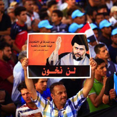 Suuren väkijoukon keskellä mies pitelee julistetta, jossa on Sadrin kuva. Sadrilla on päässään musta turbaani.