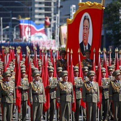 Laaja rivistö sotilaita univormuissa ja koppalakeissa seisoo punalippujen kanssa. Joukon keskellä on iso kuva Pohjois-Korean perustajasta Kim il-Sungista.