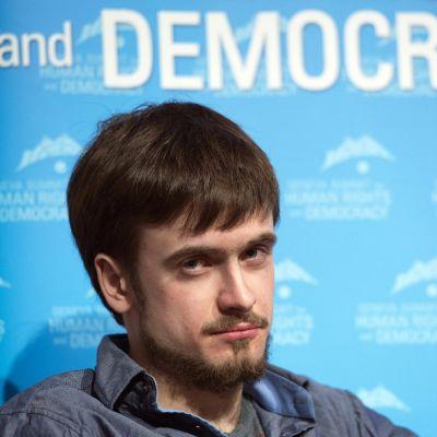 """Parrakas Verzilov katsoo vinosti kameraan päin. Hänen takanaan seinällä on valkoisilla kirjaimilla sinisellä pohjalla teksti: """"...and DEMOCRACY""""."""