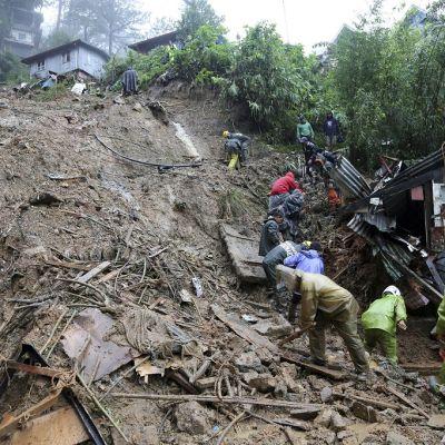 Joukko ihmisiä sadevaatteissa tutkii jyrkkää mäkeä, joka on täynnä mutaista rojua. Mäen päällä on taloja.