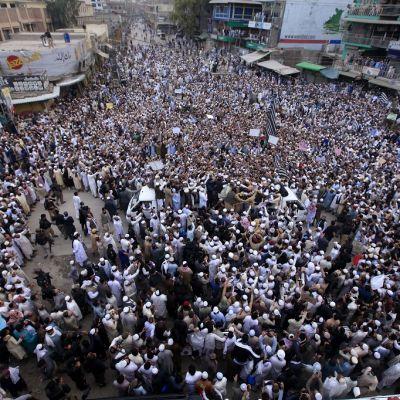 Kuvassa valtava määrä ihmisiä kadulla. Monilla on päässään valkoiset lakit. Kuva on otettu yläviistosta.