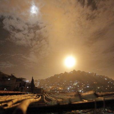 Yöllisellä taivaalla kaupungin yllä näkyy suuri keltainen valopallo.