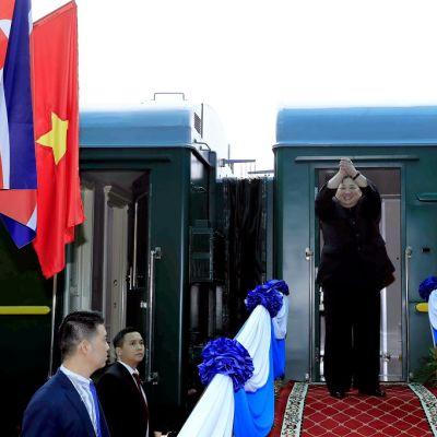 Kim seisoo junan ovensuulla hymyillen ja nostaen ristittyjä käsiään ilmaan.