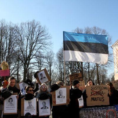 Mielenosoittajien joukolla on kylttejä, jossa on poliittikkojen kasvokuvia. Yllä liehuu iso Viron lippu.