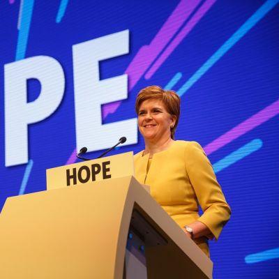 Kuvassa Skotlannin pääministeri Nicola Sturgeon lavalla puhujanpönton takana. Taustakankaalla lukee isoilla kirjaimilla teksti HOPE eli toivo.