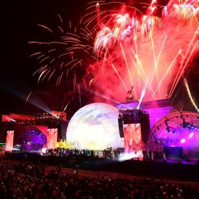 Ilotulitteita ammutaan taivaalle esiintymislavan taustalla. Takana näkyy Brandenburgin portti.