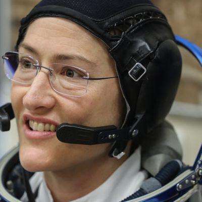 Lähikuva avaruuslentäjän asuun pukeutuneesta, hymyilevästä Christina Kochista.
