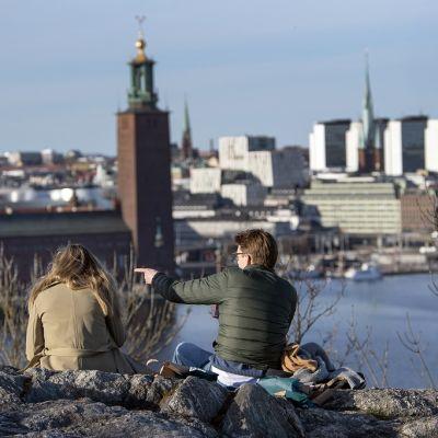 Vierekkäin, selin kameraan, istuvat kaksi ihmistä katselevat Södermalmin kallioilta Tukholman keskustaan päin.