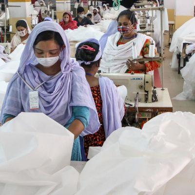 Kuvassa tekstiilitehtaan työntekijöitä Bangladeshin pääkaupungissa Dhakassa. Etualalla naistyöntekijä ja valkoista kangasta.