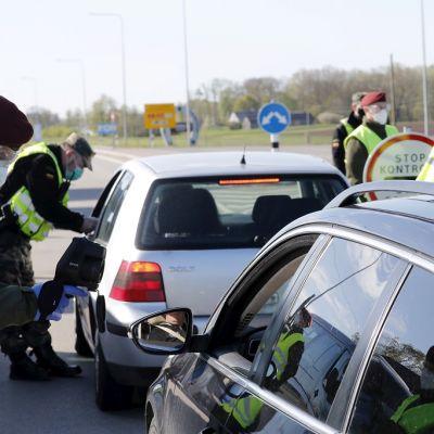 Kuvassa kaksi autoa ja neljä rajavartioston työntekijää.