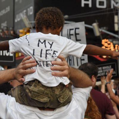 """Pieni musta lapsi selin isänsä harteilla, paidan selässä lukee """"my life matters""""."""