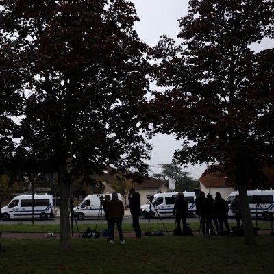Toimittajia ja valkoisia pakettiautoja koulun edessä.