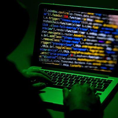 Kuvassa tietokoneen näyttö hämärässä, vihertävässä valossa. Konetta käyttävästä hahmosta näkyy pää ja selkää ja näppäimistöllä olevat kädet.