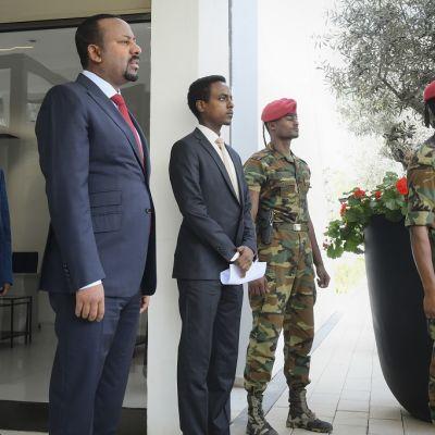 Kuvassa etualalla seisoo Etiopian pääministeri Abiy Ahmed. Hänen oikealla puolellaan on kaksi sotilasta. Lisäksi kuvassa on kaksi miestä, jotka ovat ilmeisesti Abiyn avustajia. Toinen on hänen oikealla ja toinen vasemmalla puolellaan.
