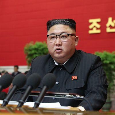Kim Jong-un istuu pöydän takana. Hänen edessään on useita mikrofoneja.