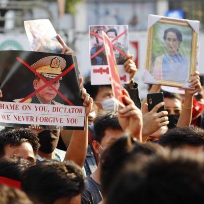 Kuvassa mielenosoittajia. Yhdessä kyltissä on kenraalin kuva ja toisessa Aung San Suu Kyin kuva.