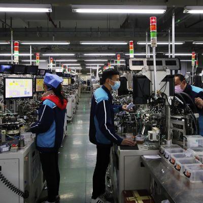Kuvassa kolme työntekijää kiinalaisella komponenttitehtaalla. Työntekijät seisovat työpisteiden ääressä.
