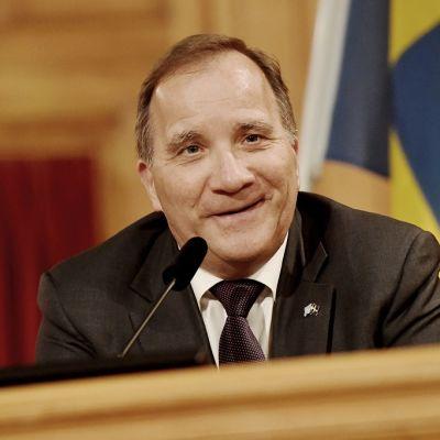 Hymyilevä Löfven taustallaan Ruotsin lippu.