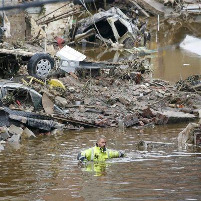 Mies kahlaa kainaloitaan myöten ruskeassa vedessä. Ympärillä täysin tuhoutuneita autoja ja muuta roimaa.