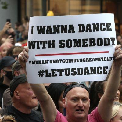 """Mielenosoittajia, joista etummainen nostaa suurta paperiarkkia. Siinä lukee englanniksi """"Haluan tanssia jonkun kanssa"""" ja """"Tanssikaamme""""."""