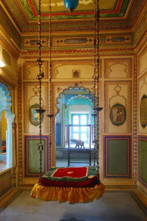 Indisk säng som hänger i taket med kättingar. Sängen utgörs av en röd-grön kvadratisk madrass av sammet.