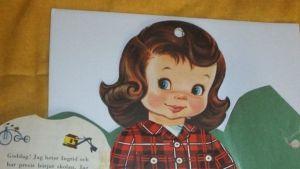En papperdsocka med brunt hår och en rödrutig kjol på sig.