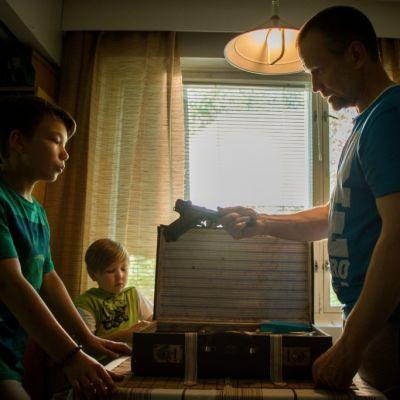 Småpojkarna Onni Tommila och Iivari Raittinen får en pistol av fadersgestalten Jorma Tommila
