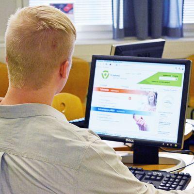 Nuori selailee TE-toimiston tietokoneella TE-palveluiden internetsivustoa.