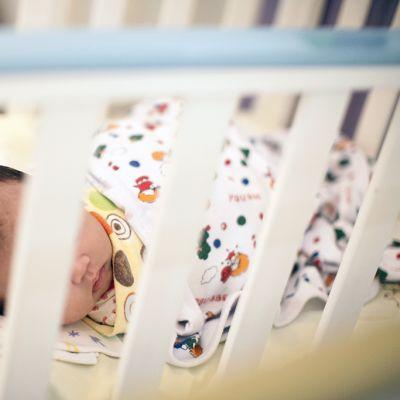 Vauva pinnasängyssä.