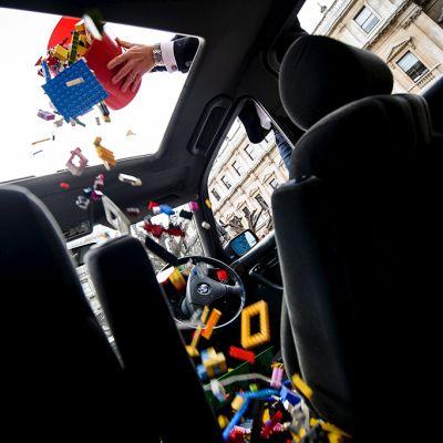 Mies tiputtaa ämpäristä Legoja autoon.