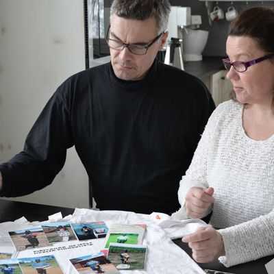 Pertti ja Marja Ylitalo katsovat valokuvia