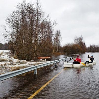 Kaksi henkilöä melovat kanootilla veden vallassa olevalla tiellä.