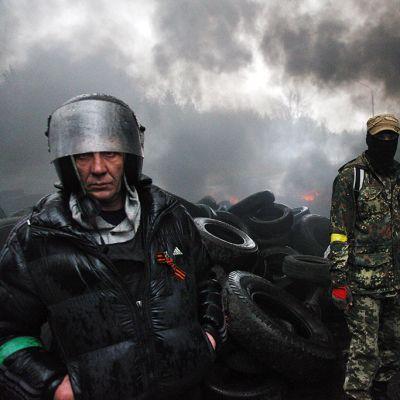 Protestoijia tiellä, taustalla mustaa savua.