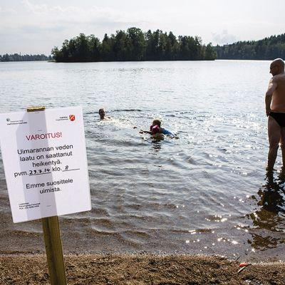 Ihmisiä uimassa ja veden laadun heikentymisestä varoittava kyltti Tohloppijärven rannalla Tampereella tiistaina 29. heinäkuuta 2014.