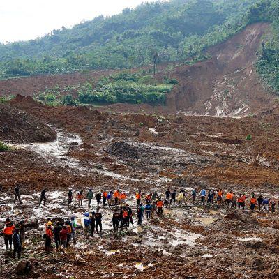Punaisiin pukeutunut pelastushenkilökunta katselee massiivista tuhoa.