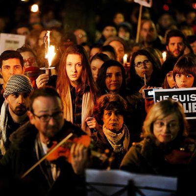 ihmisiä mielenosoituksessa kynttilöitä kädessä