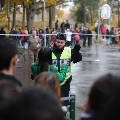 Poliisi keskustelemassa ihmisten kanssa Kronan-koulun edustalla Trollhättanissa torstaina.
