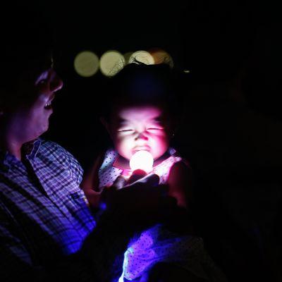 Isä ja pieni lapsi Eart Hour -tapahtumassa Pasayn kaupungissa Filippiineillä.