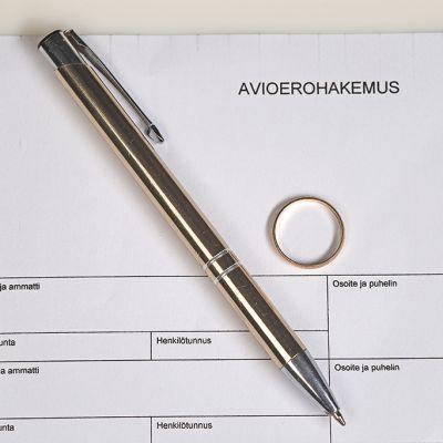 Avioerohakemus, vihkisormus ja kynä.