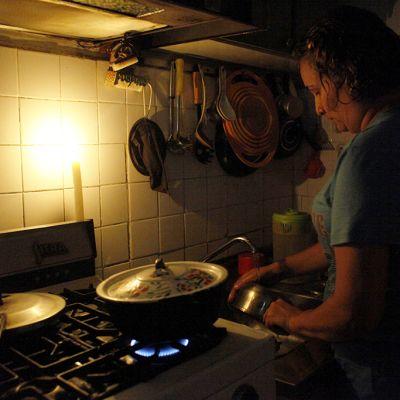 Nainen valmistaa ruokaa kaasuliedellä kynttilänvalossa säännöstellyn sähkökatkon aikana.