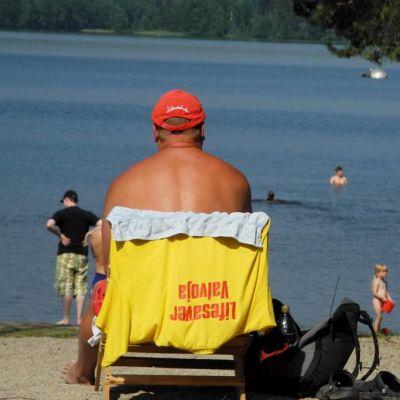 Rantavahti istuu Tuomiojärven rannallta, ihmisiä uimassa.
