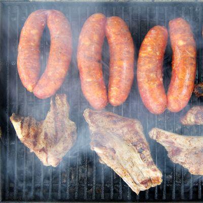 Grillissä kypsyy ribsejä ja erikoismakkaroita.