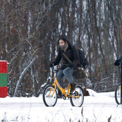 Kaksi pakolaista käyttää polkupyörää ylittäessään rajan Venäjältä Norjaan.