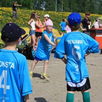 Lapset pelaavat lentopalloa ulkona.