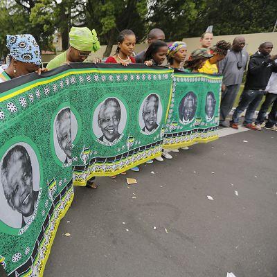 Ihmisiä kerääntyi Nelson Mandelan talon ulkopuolelle rukoilemaan. Kädessään heillä on leveä vihreäpohjainen ANC:n lippu, jossa on Mandelan kasvokuvia.