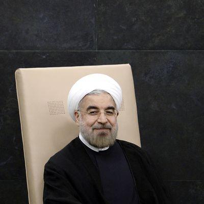 Iranin presidentti Hassan Rouhani myhäilee vaaleanruskealla tuolilla.